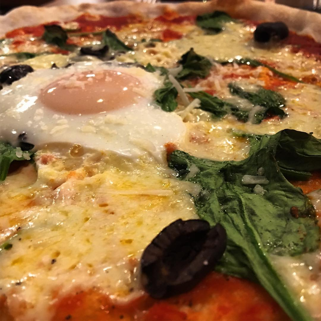 Fiorentina Pizza, a classic pizza with spinach, olives, mozzarella and an egg.