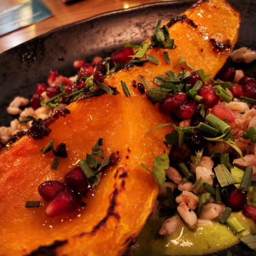 Chargrilled Crown Prince squash grown by Riverford Organic, served with kale & cashew nut mole