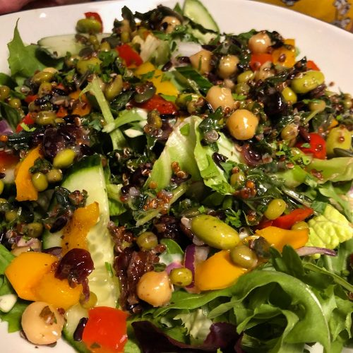 Leggera Superfood Salad, a mix of black rice, edamame beans, red quinoa, mung beans, chickpeas, cranberries, pumpkin seeds and kale in a vinaigrette, on a bed of mixed leaves, rocket, cucumber, roasted peppers, red onion and fresh parsley with our light house dressing.
