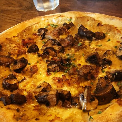 unghi Luganica - A 'white pizza' with a mascarpone and porcini base, topped with garlic & thyme chestnut mushrooms, pancetta, Luganica sausage and mozzarella.